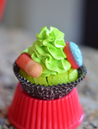 Body Part Cupcakes from Mooshu Jenne. They feature body part gummies with a green whipped topping icing and a yogurt based cupcake.