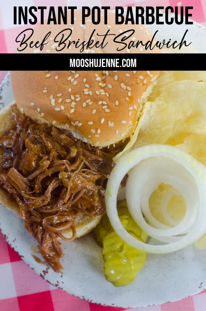 Instant Pot Barbecue Beef Brisket Sandwich on plate with onions, pickles, and chips.