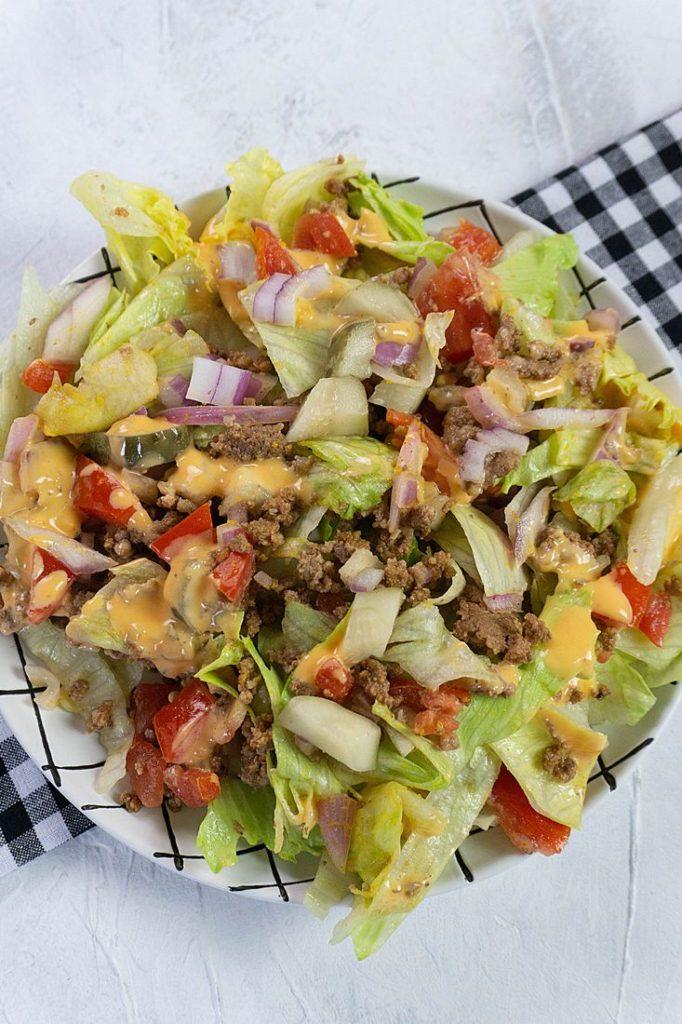 Big Mac Salad on white background with a plaid black napkin
