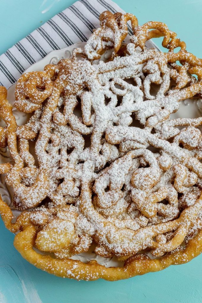 Funnel cake with powdered sugar on blue background