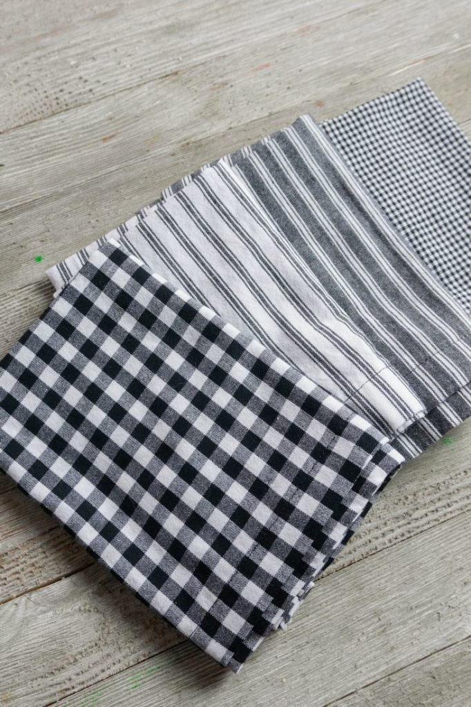 Napkins in gray, plaid,  and stripes on a wood gray board