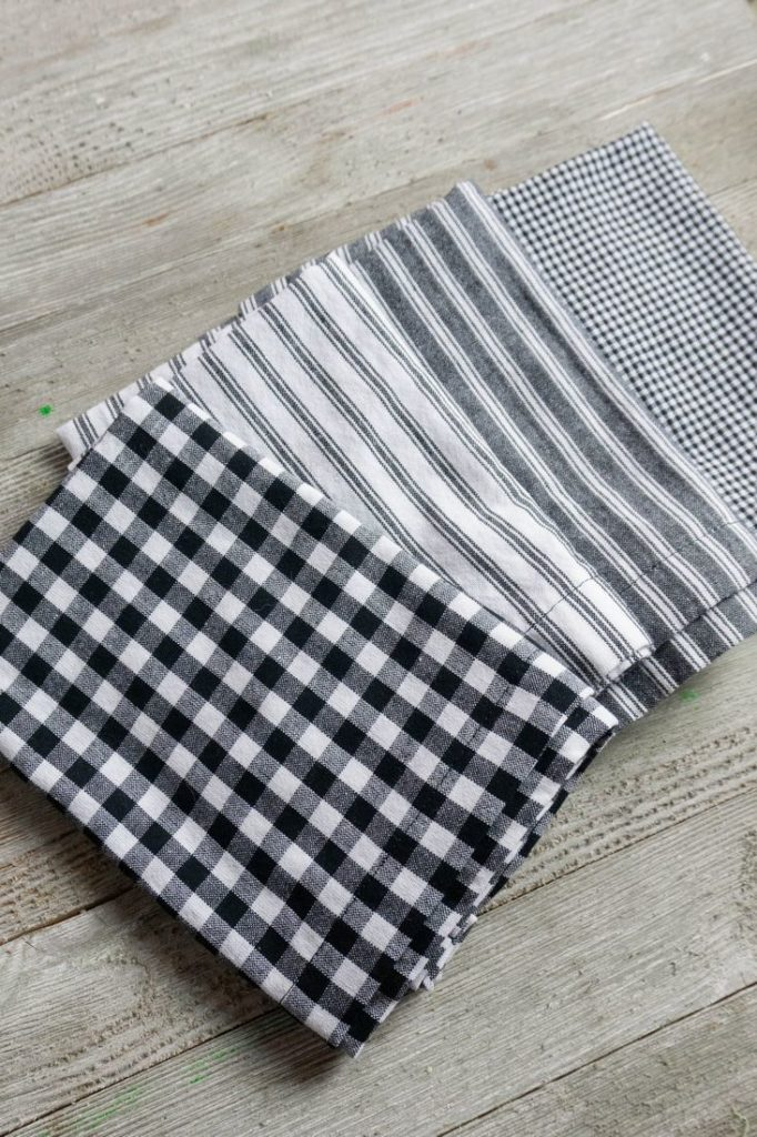 Cloth Napkins in gray, stripes, and plaid on gray wood background