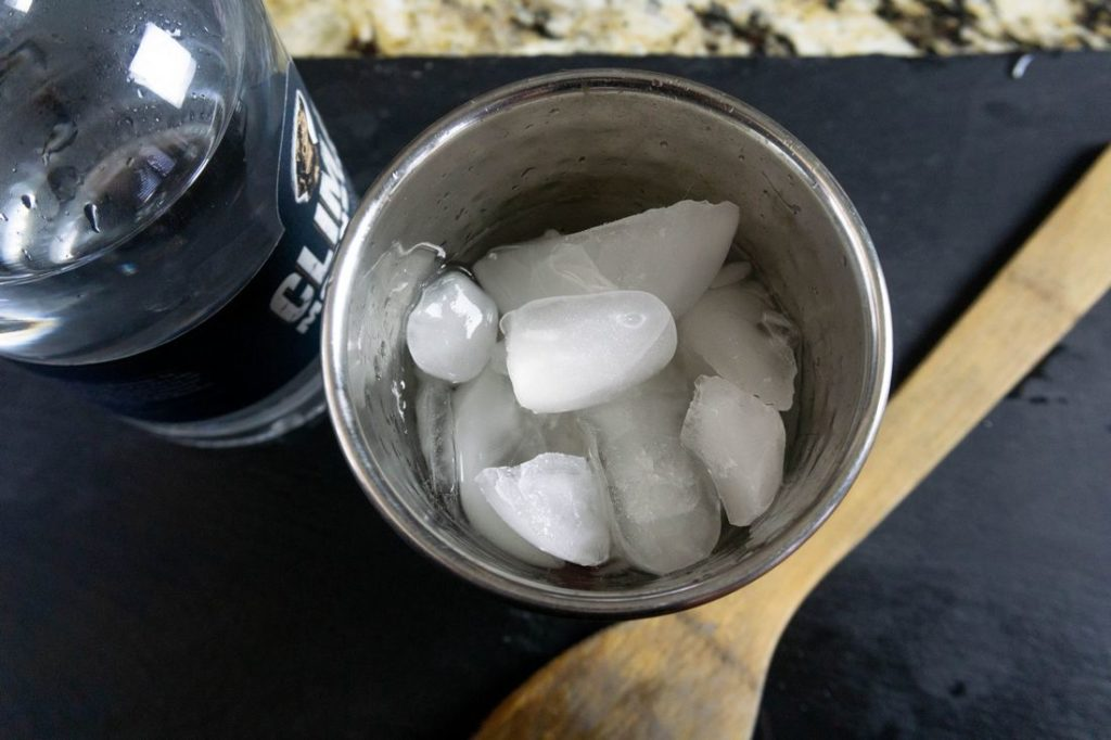 Ice in a shaker with moonshine bottle