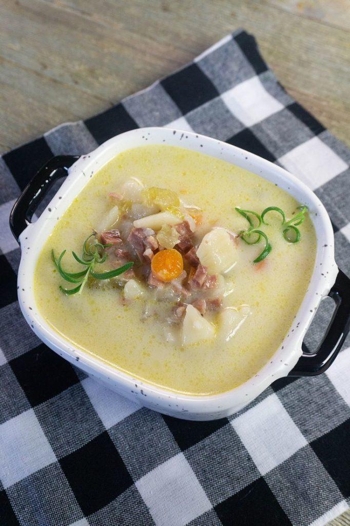 ham potato soup in a bowl on black plaid napkin