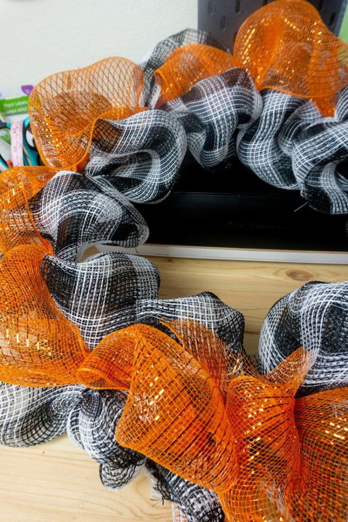wreath frame with buffalo plaid mesh attached by pipe cleaner