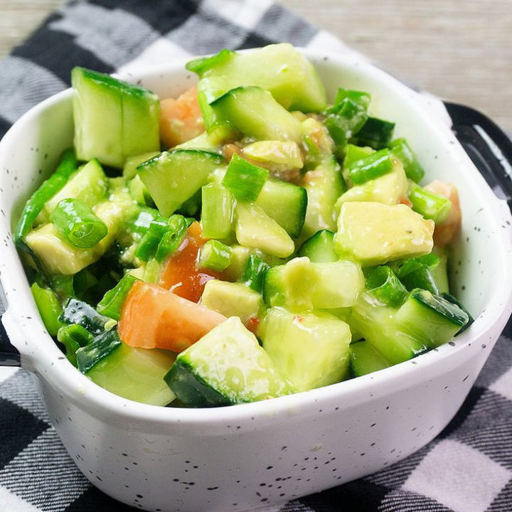 Avocado Cucumber Salad on grey backdrop with black and white plaid napkin