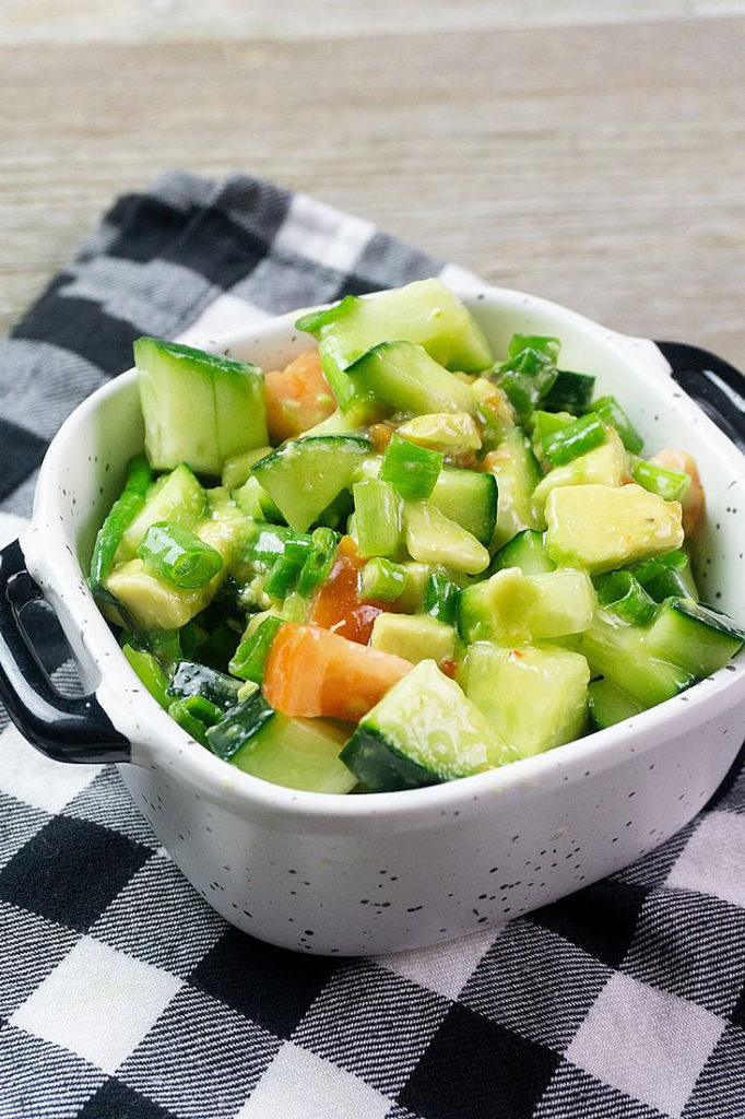 Avocado Cucumber Salad on grey backdrop with black and white plaid napkin