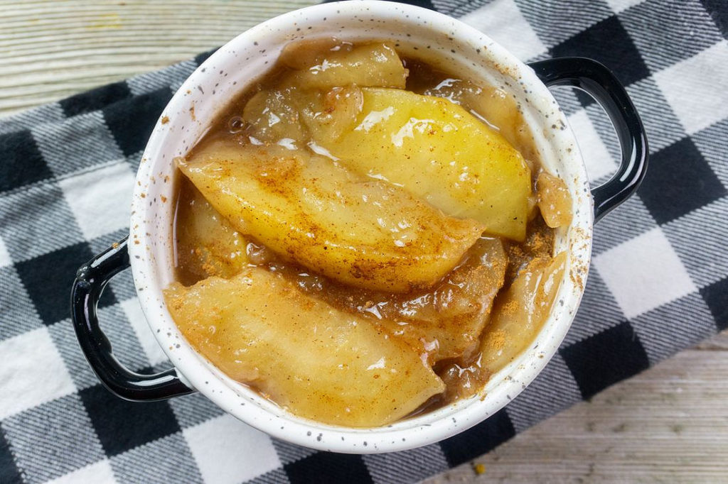 Instant Pot Cinnamon Apples on grey wood with black and white plaid napkin.