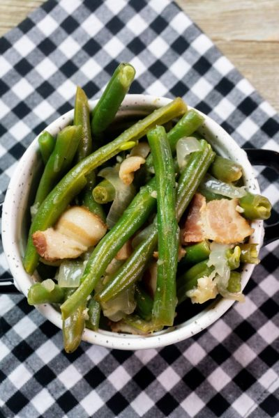 Instant Pot Bacon Green Beans inside a black and white bowl on a plaid napkin