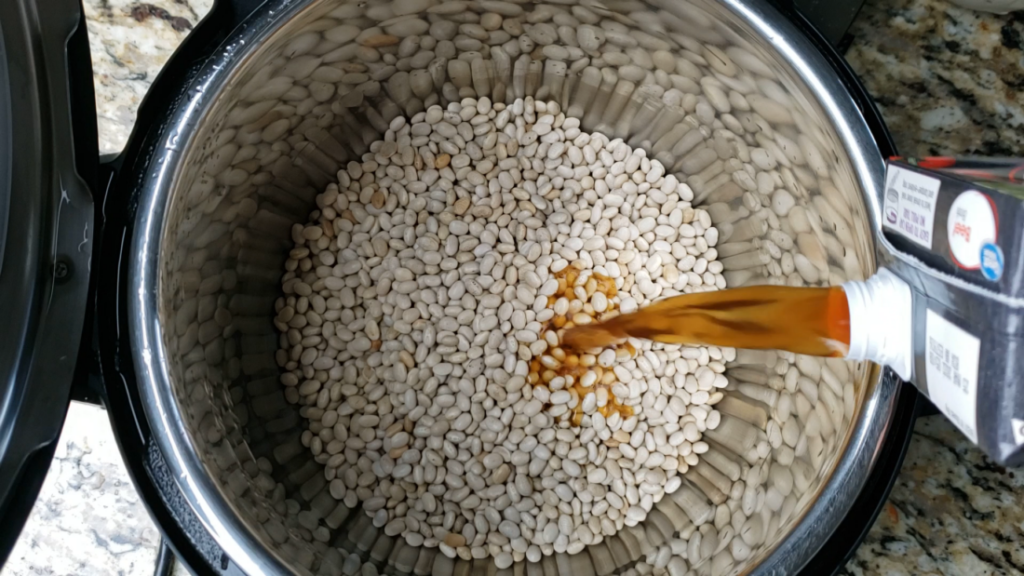 white beans inside the instant pot with beef broth pouring in