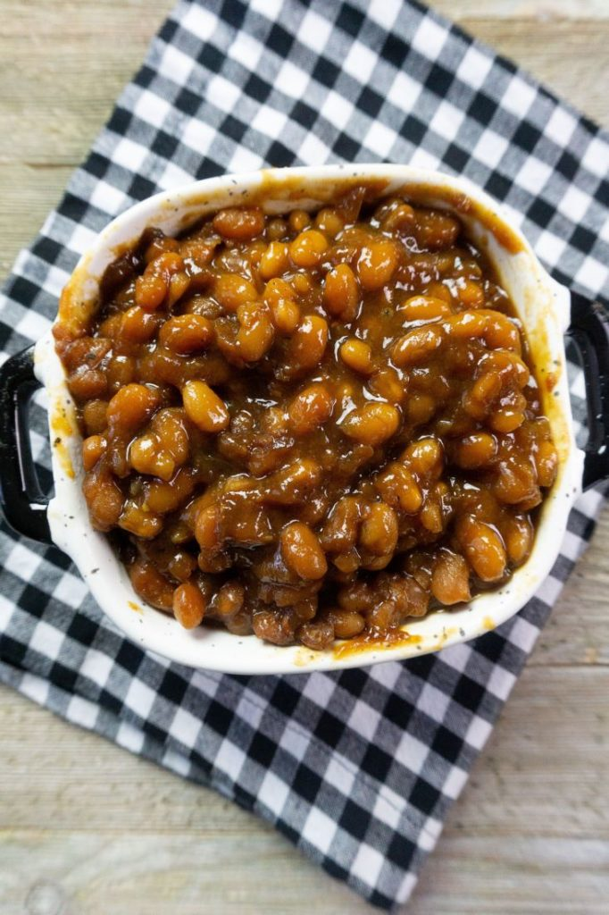 Instant Pot Baked Beans on a wood board in a black and white speckled bowl with black and white plaid napkin