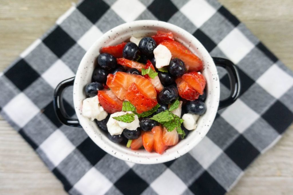 July 4th Fruit Salad with strawberries, blueberries, and mozzarella pearl cheese in a whote bowl with black speckles on a black and white plaid napkin