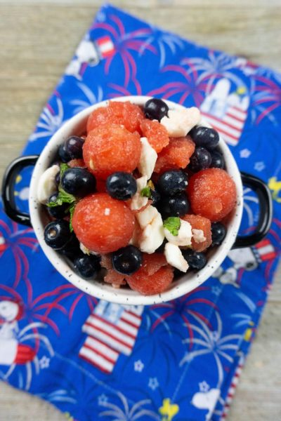 Watermelon, pearl mozzarella, blueberries, and mint in a white bowl on a snoopy cloth napkin