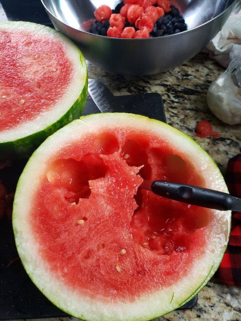 Watermelon cut in half with melon balls taken from the flesh
