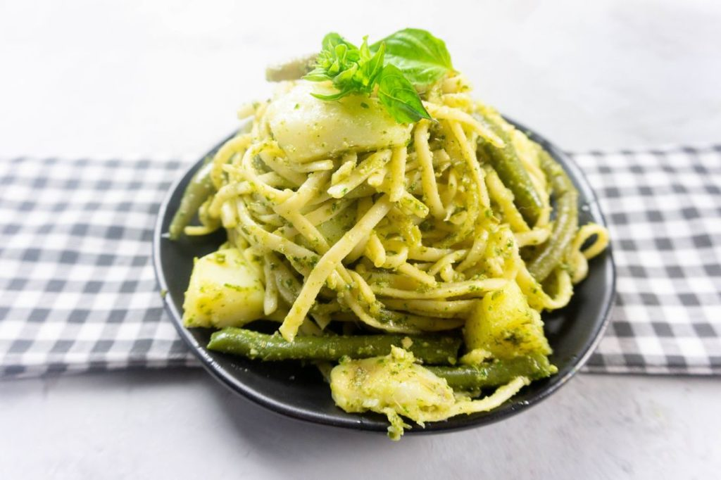 linguine noodles with pesto, potatoes, and green beans on a black plate with concrete backdrop
