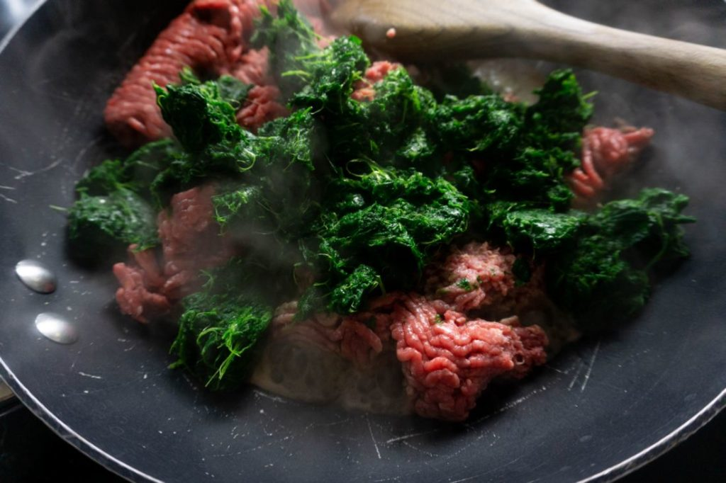 Ground beef and spinach in a sauté pan