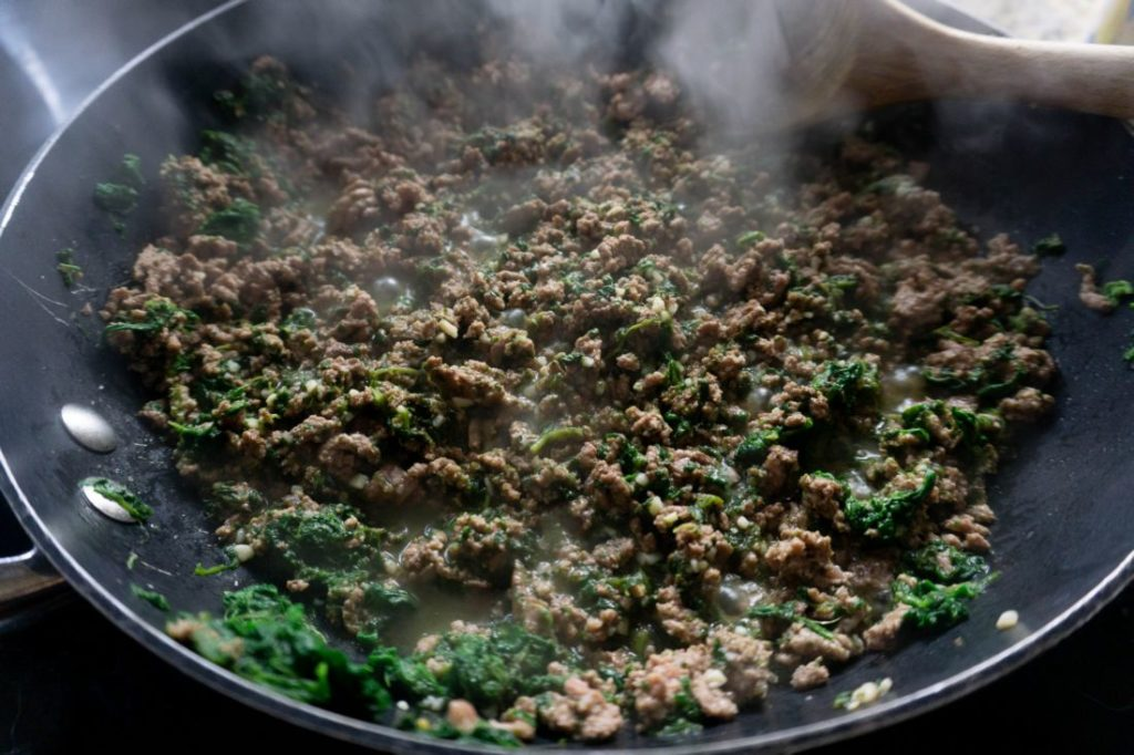 ground beef and spinach browned in a pan