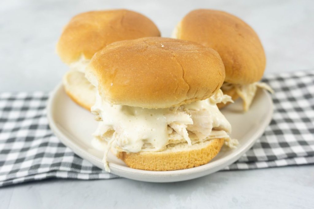 Instant Pot Alabama White Sauce Sliders on a white plate with gray plaid napkin and concrete back drop