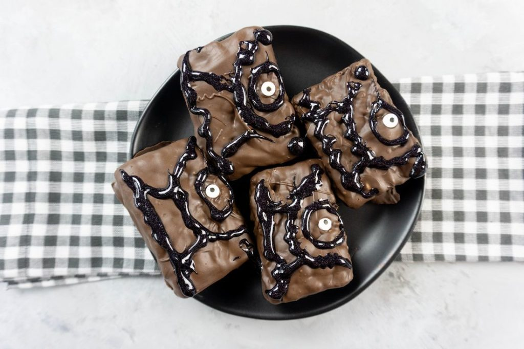Hocus Pocus Spell Book Krispies on a black plate with grey plaid napkin on a concrete backdrop