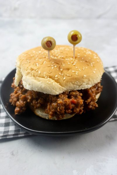 Monster sloppy joe with olive eyes and on a black plate with gray plaid napkin.