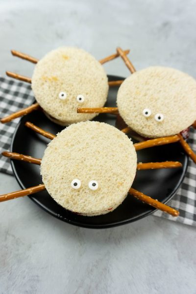 Spooky Spider Sandwiches on a black plate with a gray plaid napkin